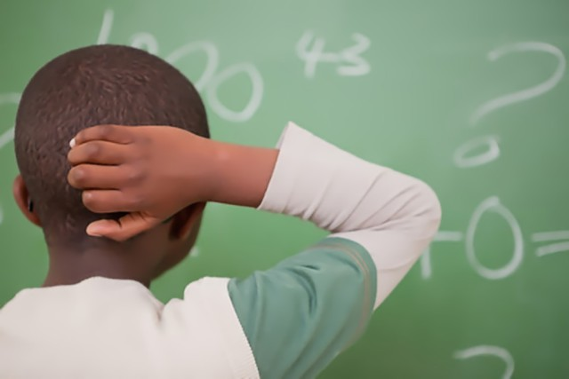 Student at board with hand on head, doing math